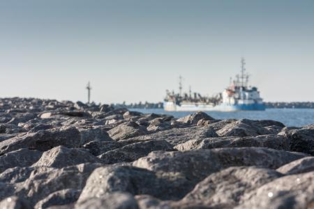 Ship leaves harbor channel of Klaipeda. 스톡 콘텐츠