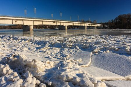 The bridge across the river. Winter, large ice drifts.