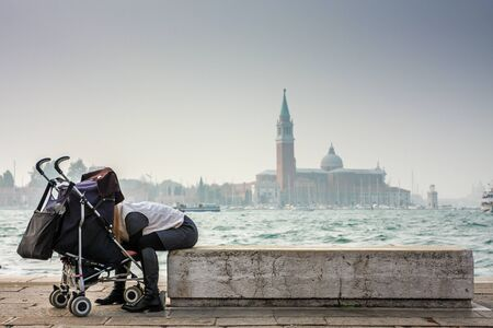 Young woman looking at her baby in stroller. 스톡 콘텐츠