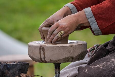 shaping: Traditional pottery making, close up of potters hands shaping a bowl. Stock Photo