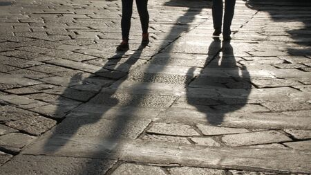 Silhouettes of people on the cobblestone pavement, evening. 스톡 콘텐츠