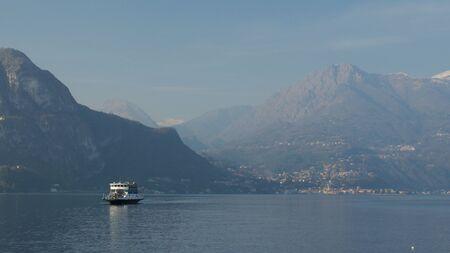 Ferry sailing through a mountain lake. Lake Como, Italy. February