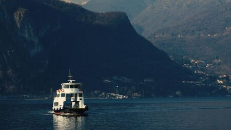 Mountains in the background ferry with passengers, Lake Como, Italy.