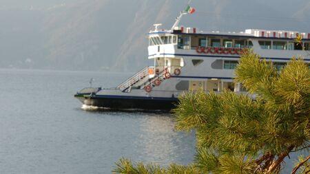 Lake Como, Italy - February 28, 2017 : ferry boat sailing through a mountain lake. 스톡 콘텐츠