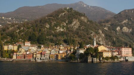 The beautiful shores of Lake Como with the town of Varenna and the Italian Alps in background. View from ferry.