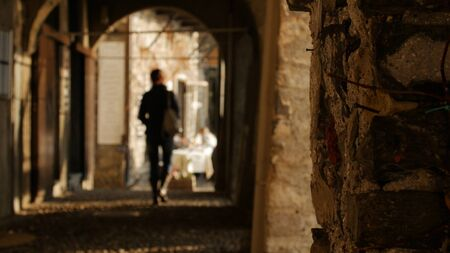 Young woman walking through the arches of the historical buildings away from the camera. 스톡 콘텐츠