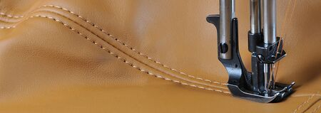 subtlety: sewing machine sews the orange line on the skin