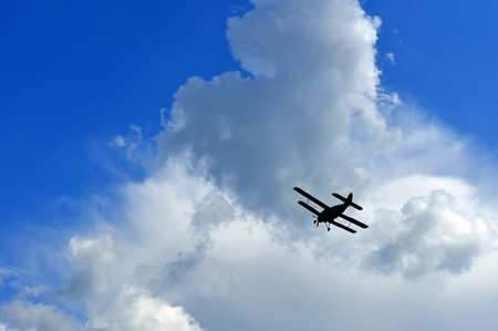 Plane in the sky under the clouds photo