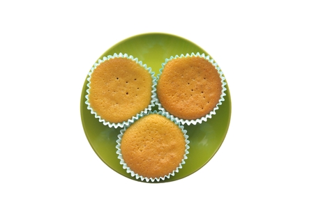 Three cupcakes on a green plate on a white background photo