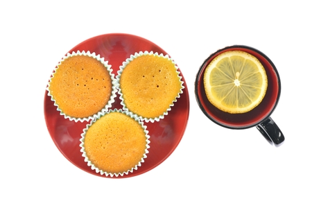 stand teapot: Three cupcake on a red plate on a white background