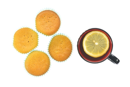 Muffins and a cup of tea with lemon on a white background photo