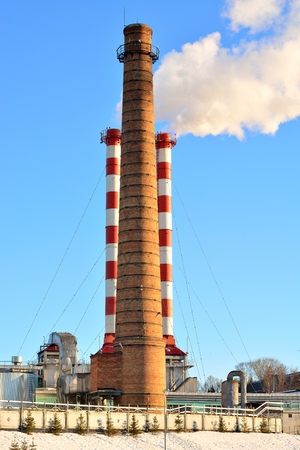 boiler house: Smoking chimneys city boiler house in the winter against the blue sky Stock Photo