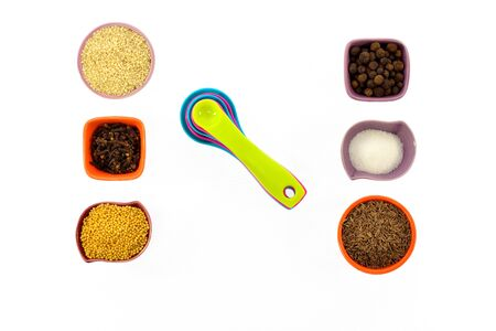 measuring spoons: Seeds, spices, grains in small multi-colored cups and measuring spoons on a white background Stock Photo
