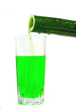 Cucumber juice is poured into a glass of cucumber on a white background