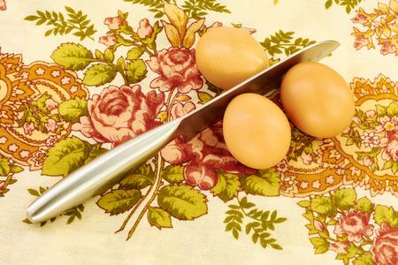 breaks: Steel knife breaks the eggs on a napkin Stock Photo