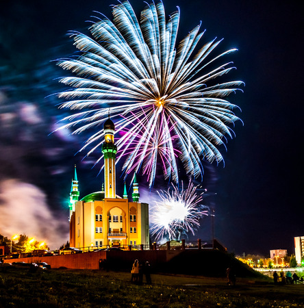 Fireworks in the city on the background of a Muslim mosque