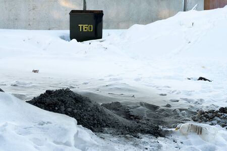 salvage yards: Ashes thrown into the snow next to a container for waste Stock Photo