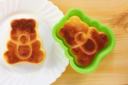 shape cub: Cinnamon cake in the shape of a bear cub on a wooden table