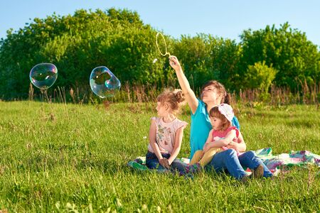 Mother with her two daughters in a park blow bubbles photo