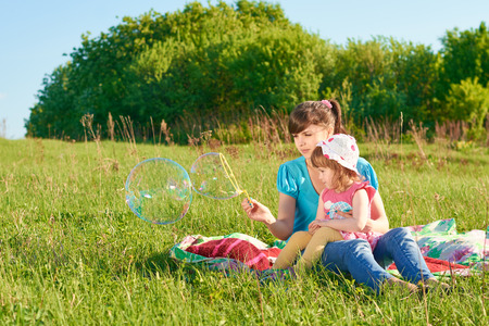 Mom and daughter in the park blow bubbles photo