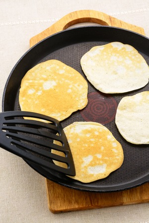 griddle: Ruddy pancakes on a black frying pan Stock Photo