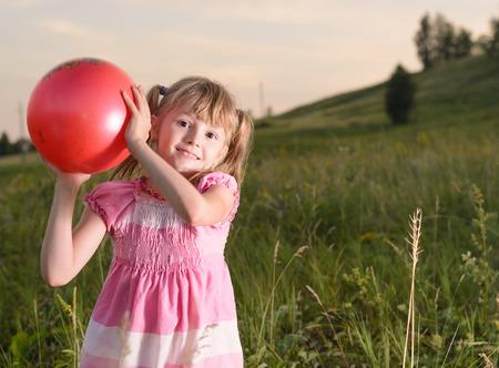 Niña jugando con una bola roja en el parque de verano Foto de archivo - 41919825