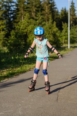 inline skater: The girl rollerblading in a helmet in the summer park