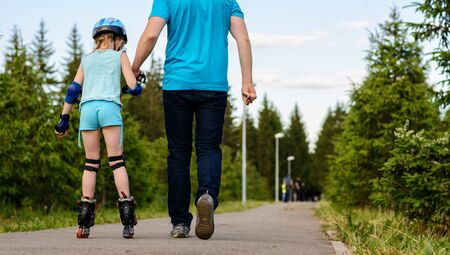rollerskating: Girl roller-skating in the park with dad