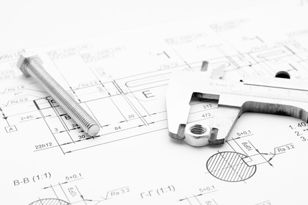 architectural architect: Bolt, nut and caliper lie on the drawing
