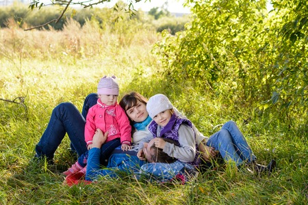 Family resting in the meadow on a sunny autumn day
