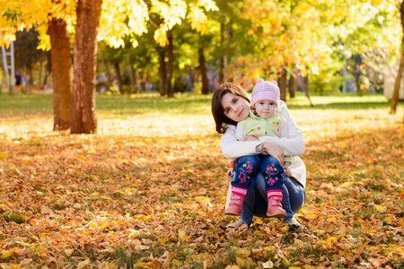 mama e hija: Madre con un abrazo bebé en el parque del otoño