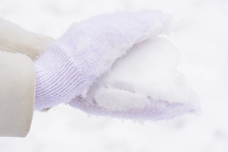 mittens: Female hand in white mittens and snow