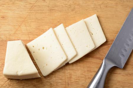 queso blanco: Cortar el queso en una tabla de madera y un cuchillo