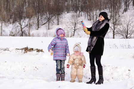 party poppers: Mother with children cracker explodes outside in winter Stock Photo