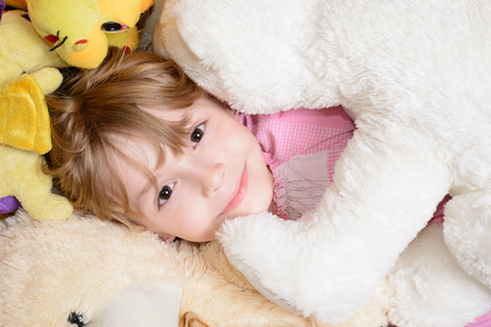 stuffed toys: Little girl lies among stuffed toys and smiling Stock Photo