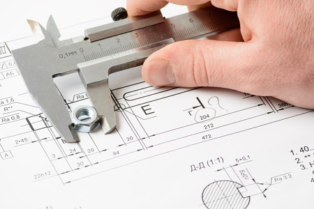 caliper: Mans hand with a caliper measuring a nut on the drawing
