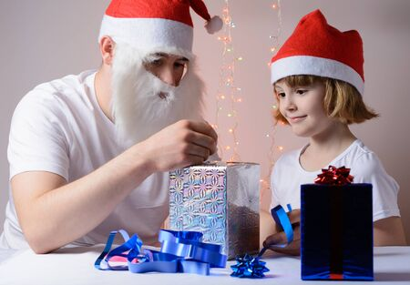 gift packs: Little girl and father in Santa hats Christmas gift packs