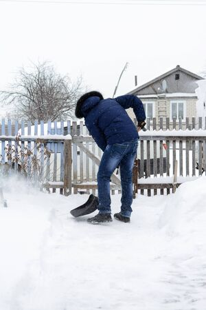 weather: Young man in a blue jacket removes snow shovel in the yard of a black Stock Photo