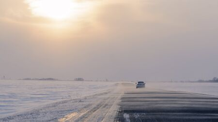 sweeps: Snowstorm sweeps across the highway snow sunlight breaks through the clouds Stock Photo