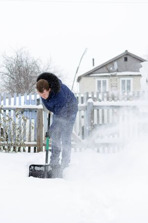 Young man in a blue jacket removes snow shovel in the yard of a black Stock Photo