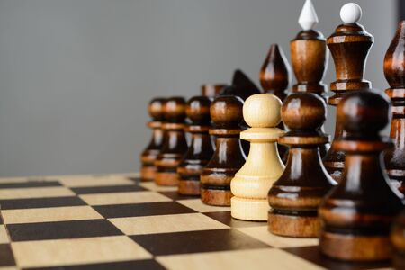 The white pawn among black pieces on the chessboard Stock Photo
