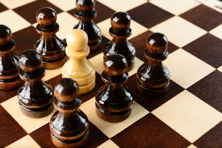 pawns: White pawn surrounded by black pawns on a chessboard