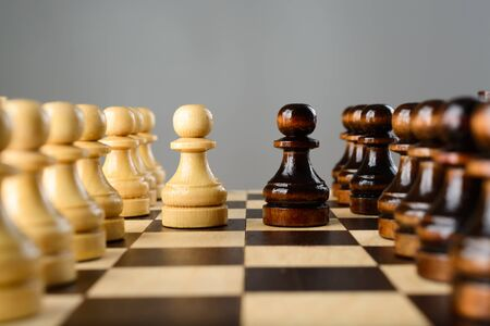 facing each other: Black and white pawns facing each other on a chessboard Stock Photo