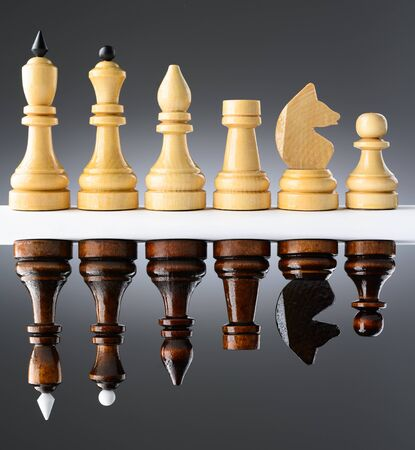 Black and white chess pieces on a white table on the gradient background