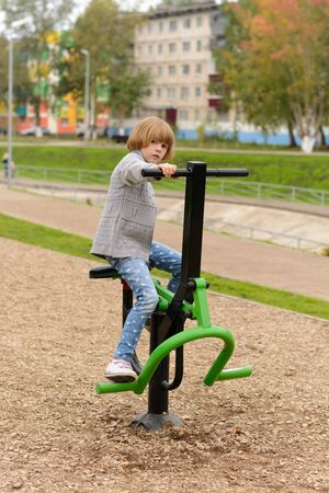 simulator: Little girl with blond hair playing sports simulator in the park Stock Photo