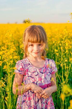 bebes niñas: Chica con el pelo rubio en un campo de flores amarillas