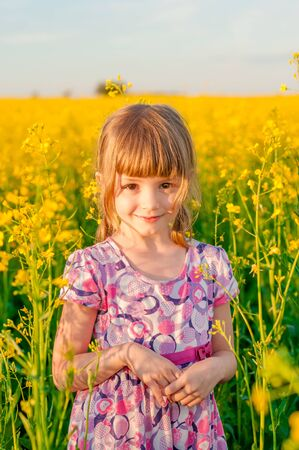 pretty baby: Girl with blond hair in a field of yellow flowers