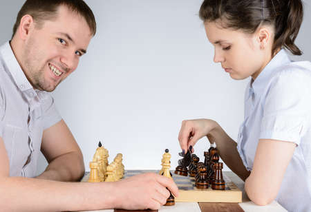 Girl playing against men and was going to go black pawn in chess Banco de Imagens