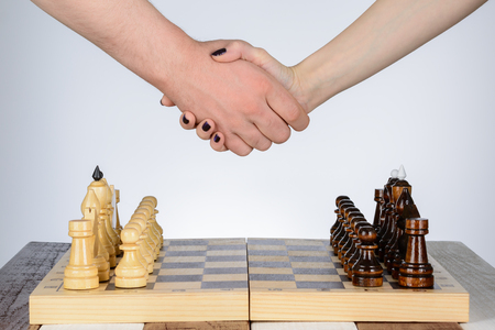 pawn to king: Male and female hand over a chess table Stock Photo