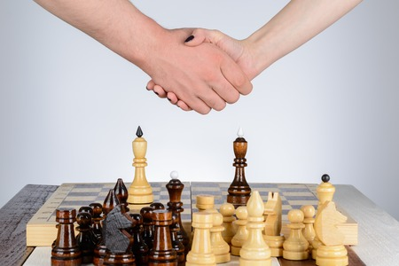 king and queen: Male and female hand over a chess table Stock Photo